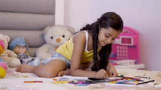 Adorable young Indian child with curly hairs making drawing and coloring at home