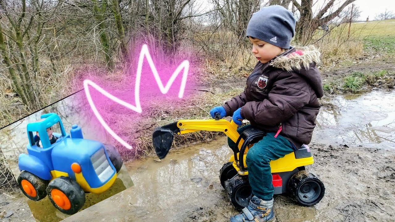Малыш весело играет с машинками игрушками. Синий трактор ...