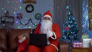 Bokeh shot of a happy Santa Claus preparing for Christmas presents using a laptop