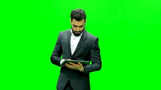 Young man dressed formally using tablet and making hand movements on virtual green screen