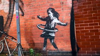 Banksy has once again left his mark, this time on a street in nottingham, england. latest mural shows child who fashioned hula hoop out of bicy...