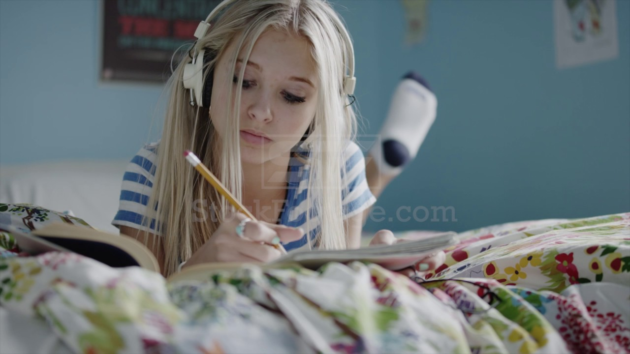 Medium shot of teenage girl doing homework and listening to music on  headphones on bed