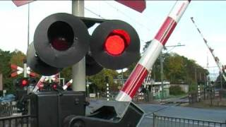 TRAIN PASSES BY VERY QUICKLY AT RAILROAD CROSSING / Spoorwegovergang in Bilthoven