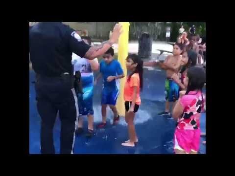 Officer Ahmed Alagha plays at the splash park with kids in Bergenfield.