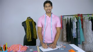 Indian male fashion designer happily smiling while working in his fashion studio
