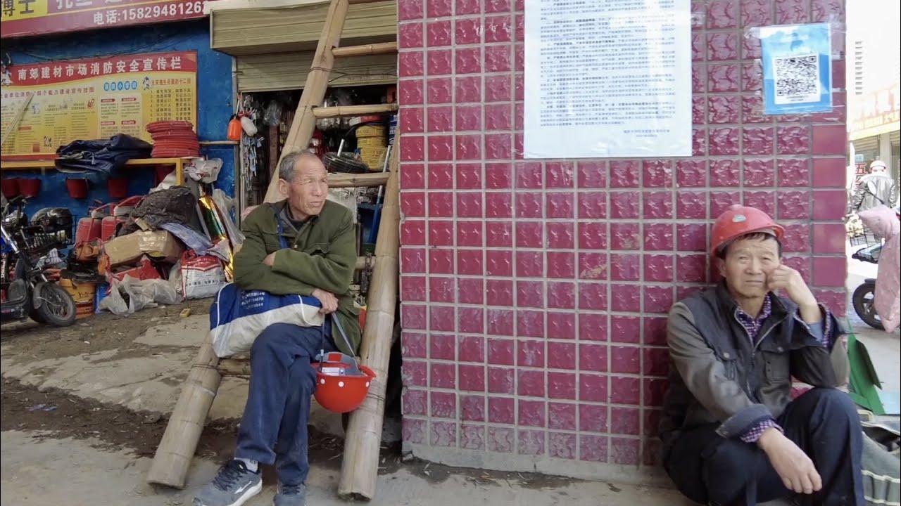 一大群農民工站在市場門口等活幹,靠打散工養家糊口。水果市場好冷清