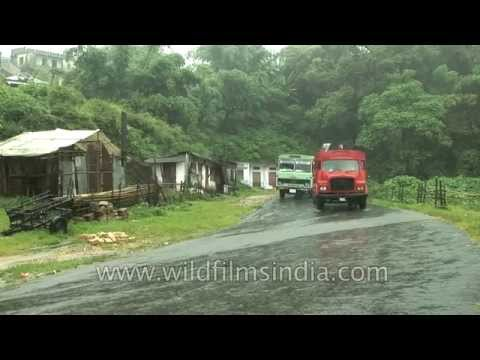 Heavy downpour of rain in Cherrapunji : fire engine and bus race on water-logged roads