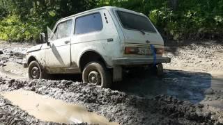 Нива, с заваренным редуктором заднего моста, выползает из грязи.