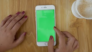 Woman / female using a smartphone (Scroll, Pinch, Click) with green screen on a wooden table