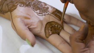 Closeup shot of a mehndi (heena) artist applying mehndi on the hands of an Indian bride