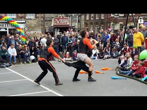 Street Circus Act Juggling Unicycles Tightrope men in Slacks