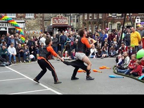 Street Circus Act Juggling Unicycles Tightrope men in Slacks