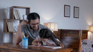 Indian father helping daughter in her studies by siting with her as she writes