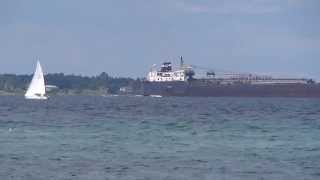 Freighter Passing A Sailboat In the Straits Of Mackinac