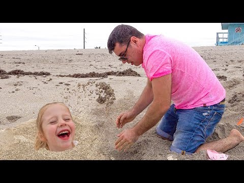 Stacy e papai brincam no mar na areia