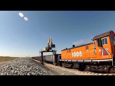 Straddle Excavator Unloading Gravel Railcars