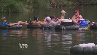Tubers float the river with cans in hand