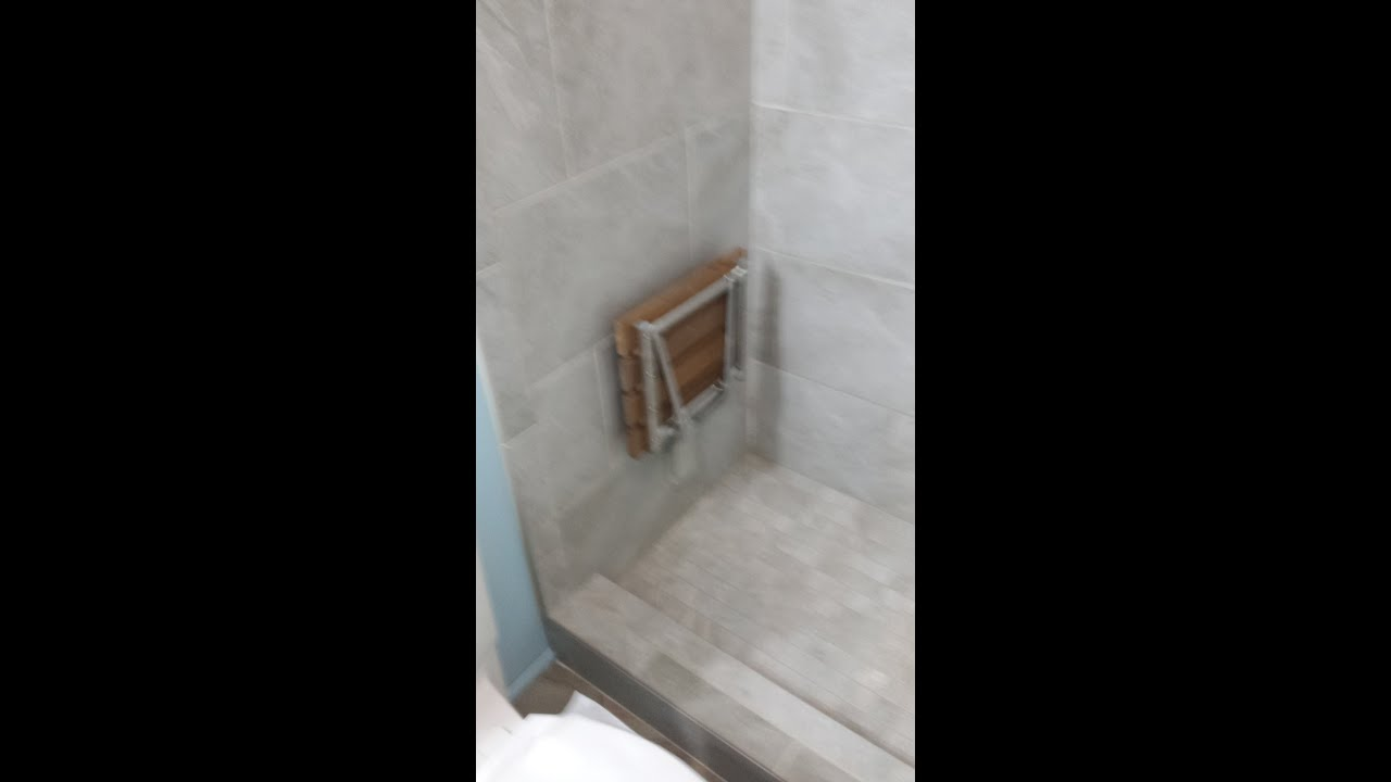 Handicap shower bench that folds away in a tile shower. - YouTube
