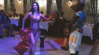 Красивое выступление восточной танцовщицы и африканского барабанщика в ресторане