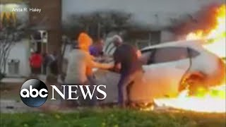 Bystanders rescue woman trapped in burning car