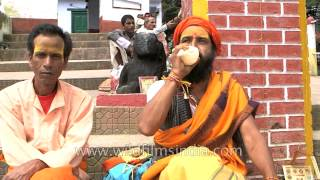 Sadhu blowing the conch shell at goddess Varahi temple