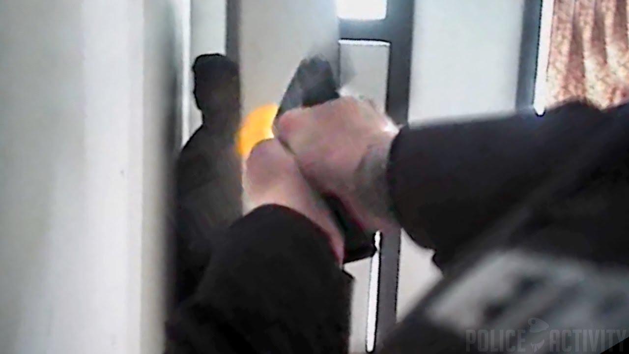 マットの裏に隠れている男性に向かって発砲するアメリカの女性警察官。