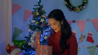 Happy Indian woman in winter wear excitedly opening her Christmas present