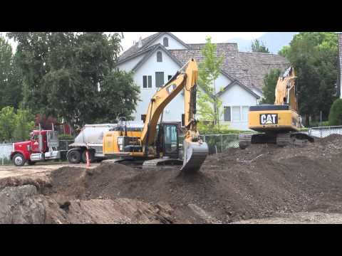 CAT 329E and 345D Excavator digging and loading multiple big rig load king double dump trucks while