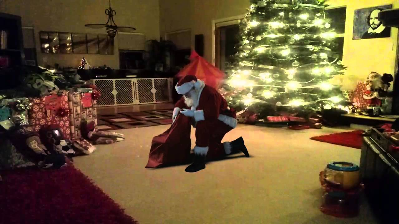 santa putting presents under the tree - caught on camera at the ...