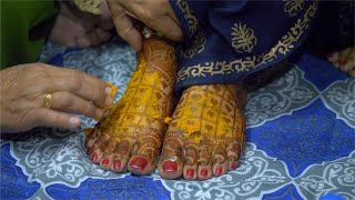 Hands of an old woman smearing Haldi (Tumeric) on Indian bride's feet painted with mehndi