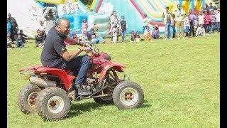 Uhuru Kenyatta carries his wife on a motorcycle