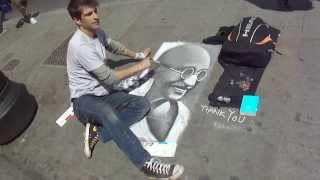 Man chalk sketching Mahatma Gandhi on pavement, Camden Market, London, UK; 3rd August 2012