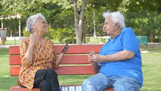 Old happy couple playing card games while sitting on a park's bench - leisure time