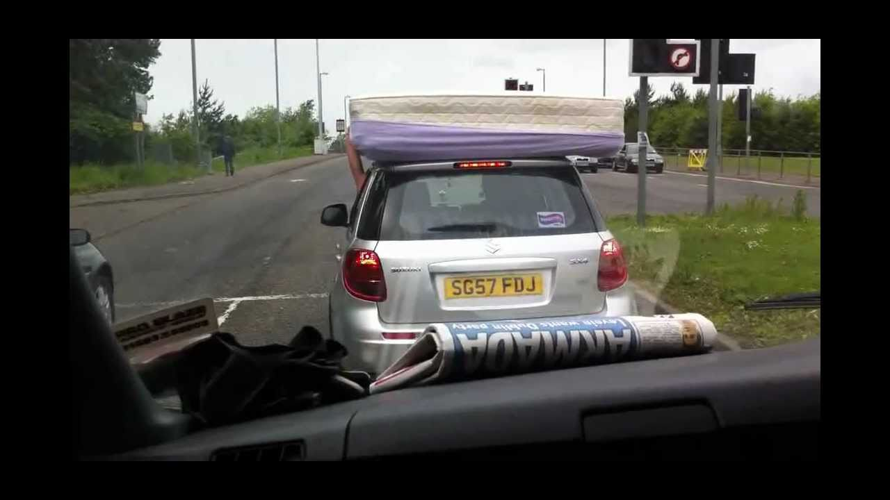 Crazy Driver And Passenger Hold Mattress On Roof Of Car Avi