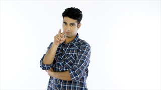 Handsome Indian man doing 'I am watching you' sign against the white background