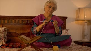 Indian woman practicing knitting sitting on the bed with a book on her side