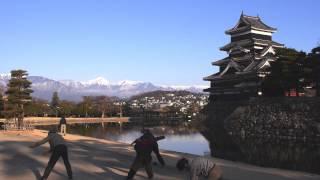 青空に北アルプスの白い稜線が映える早朝。 松本城公園で朝日を背に浴び...