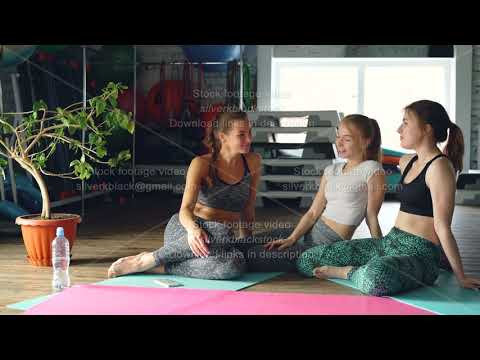 cheerful-girls-are-socialising-in-wellness-center-sitting-on-yoga-mats-on-wooden-floor.-sports
