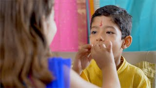 Raksha Bandhan - A young naughty brother stuffs entire sweet in his mouth given by her sister