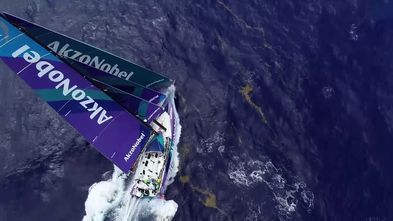 Pretty drone shots of AkzoNobel surfing on starboard through blue water and occasional sargasso weed.