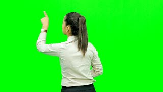 Young girl dressed formally standing against the green screen doing virtual gestures