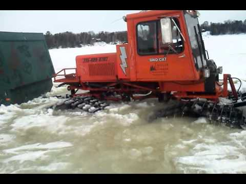 Tucker Sno Cat removing ice shack from slushy frozen lake ...