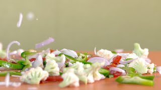 Chopped vegetables falling on a wooden chopping board