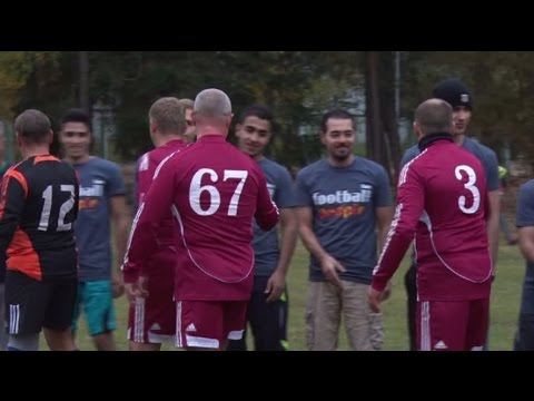 Members of parliament play football with refugees in Latvia