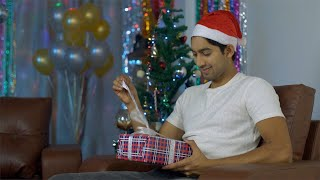 Excited young man opening his colorful Christmas present - festive scene in India