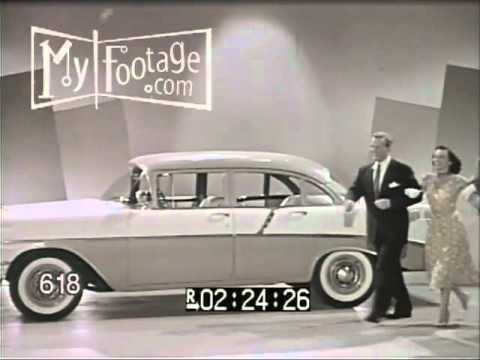 1950s SALESMAN SELLING 1956 CHEVROLET CAR TO COUPLE