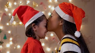 Pretty Indian mother kissing and hugging her daughter on Christmas Eve