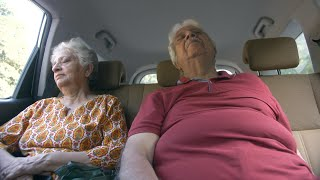 Old Indian couple sleeping in the back seat of a moving car - senior lifestyle concept