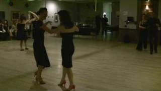 Vera leading Maria in Salsa at Paper Moon Dance Studio Carnival Dinner Dance Party