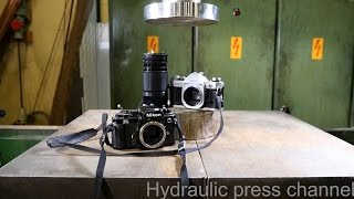 Crushing old cameras with hydraulic press